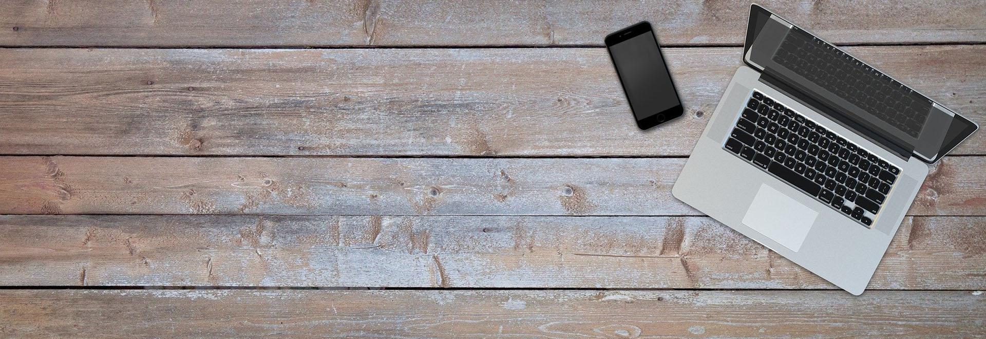Auf diesem Bild ist ein Laptop und Smartphone von oben auf einem Tisch zu sehen
