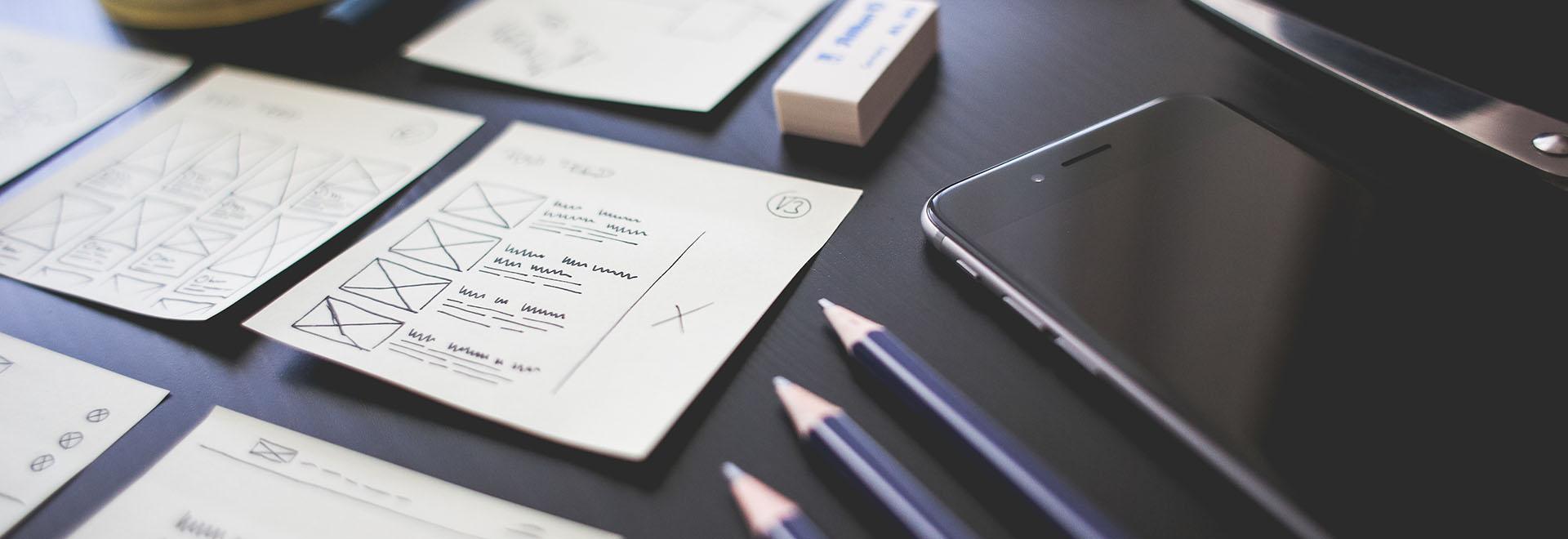 Auf diesem Bild ist sind Bleistifte, Smartphone und Notizzettel zu sehen